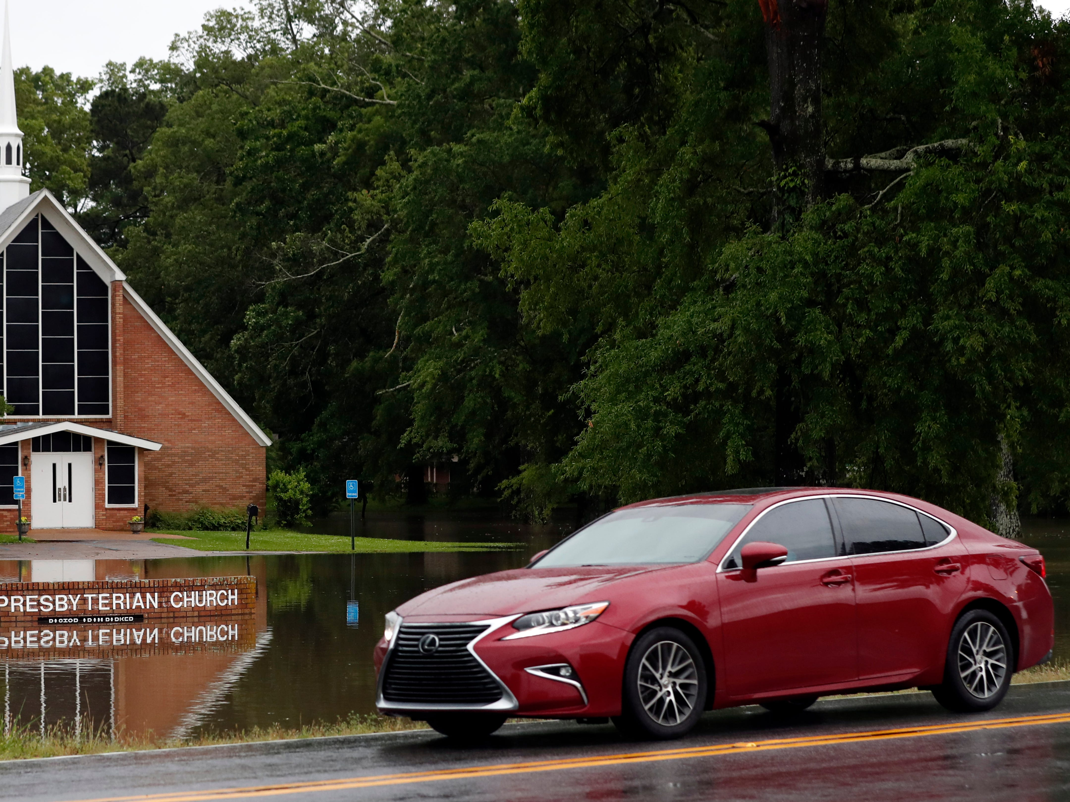 Drivers pass the Pearl Presbyterian Church's sign reflected in floodwaters covering the parking lot in in Pearl, Miss., Thursday, May 9, 2019. Strong winds, tornado warnings and substantial rains added to the flash flooding throughout Mississippi.