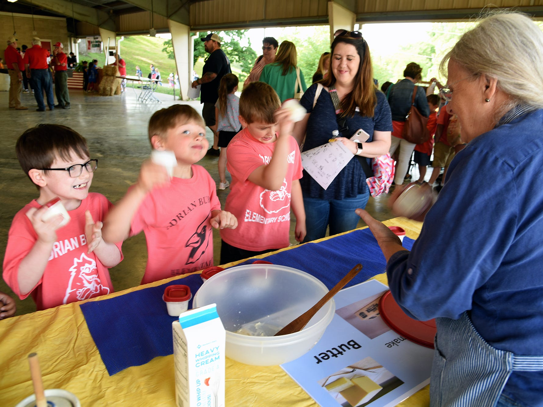 Ann Crawford, right. directs Andarian Burnitt students Cody Britt, Colton Graves, and Brayden Johnson in a butter making demonstration. Over 600 Knox County School children attended the annual Knox County Farm Bureau Ag in the Classroom Farm Day at Chilhowee Park Tuesday, May 7, 2019.