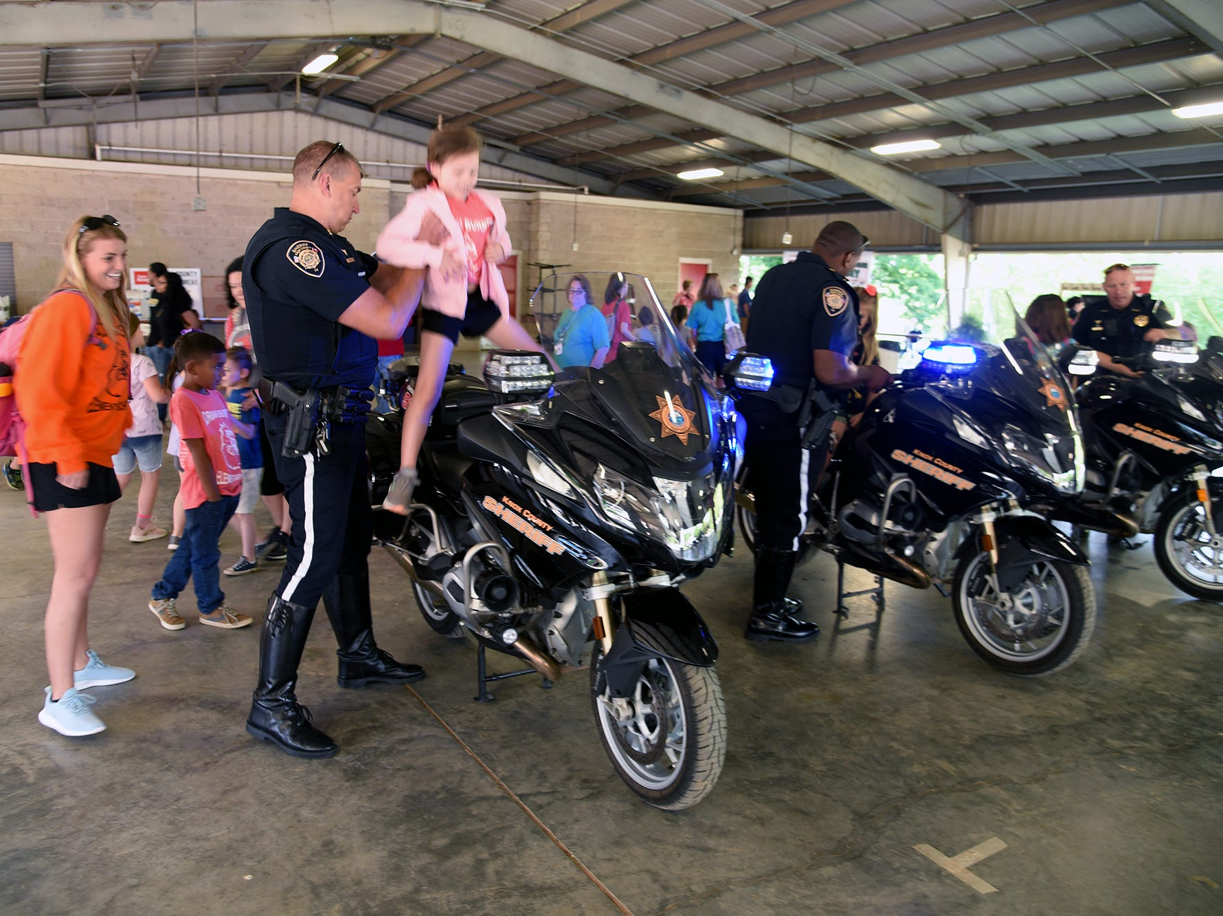 Knox County Sheriffs Department motorcycle officer Brian Rehg helps Briella Ellis,t, Adrian Burnette student onto his Motor Cycle.Over.  Over 600 Knox County School children attended the annual Knox County Farm Bureau Ag in the Classroom Farm Day at Chilhowee Park Tuesday, May 7, 2019.