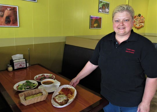 Tina Cox delivers a platter of chicken parmesan. As one of the first employees, Cox started in January, helping with the remodel of the restaurant.