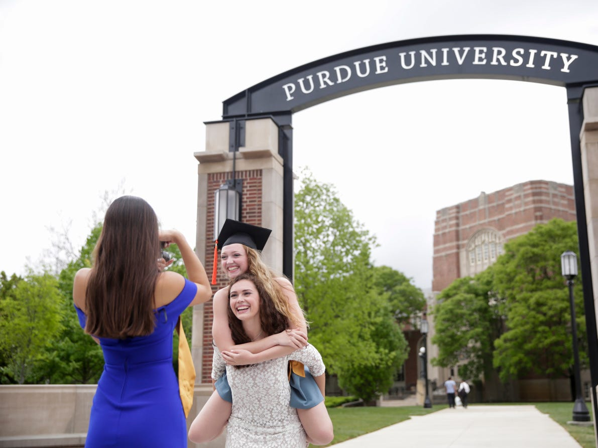 Maria Conversa smiles as she poses on her younger sister, Julia Conversa's back as Emily Adaniya takes their photo in front of the new gateway at State and Grant streets, Thursday, May 9, 2019, at Purdue University in West Lafayette. Purdue finished its new $1.9 million gateway in time for this weekend's commencement ceremonies. The gateway was built to mark the university's 150th year.