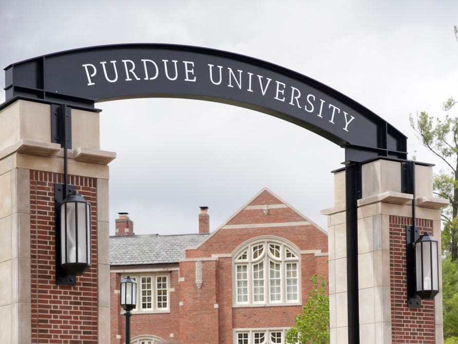 Thomas Ault, left, watches as Taylor Devine poses for photos in front of the new gateway at State and Grant streets, Thursday, May 9, 2019, at Purdue University in West Lafayette. Purdue finished its new $1.9 million gateway in time for this weekend's commencement ceremonies. The gateway was built to mark the university's 150th year.