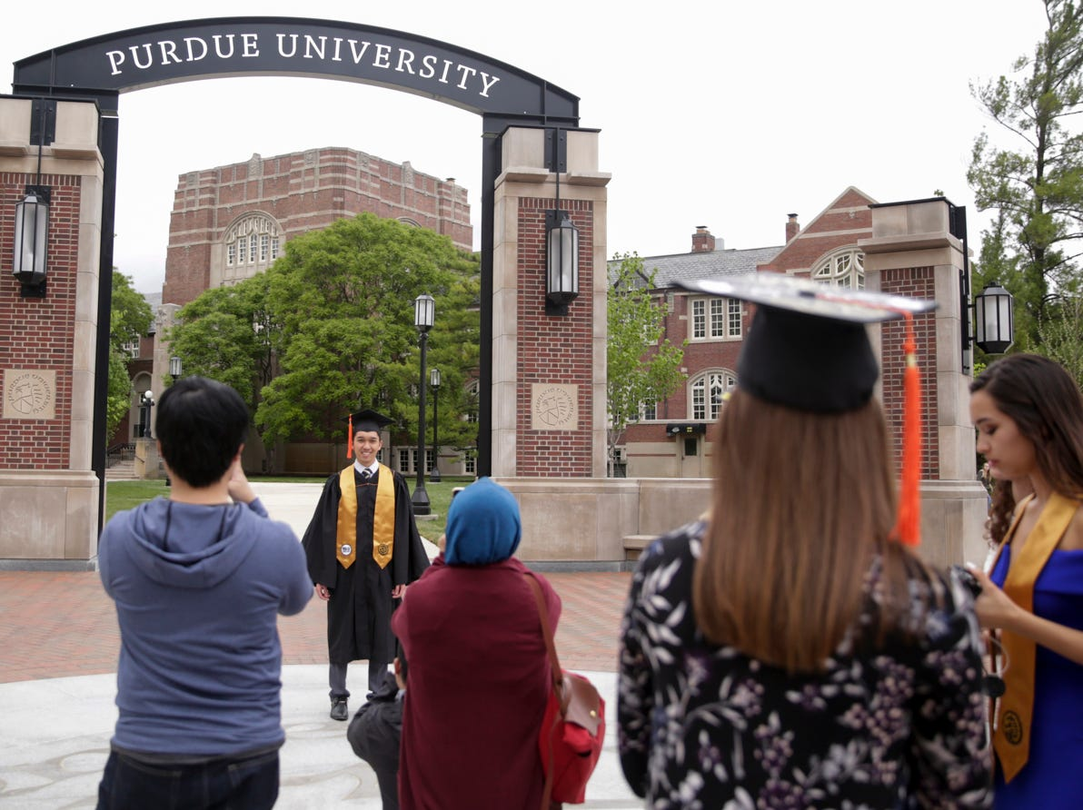 Syafi Sani poses for photos in front of the new gateway at State and Grant streets, Thursday, May 9, 2019, at Purdue University in West Lafayette. Purdue finished its new $1.9 million gateway in time for this weekend's commencement ceremonies. The gateway was built to mark the university's 150th year.
