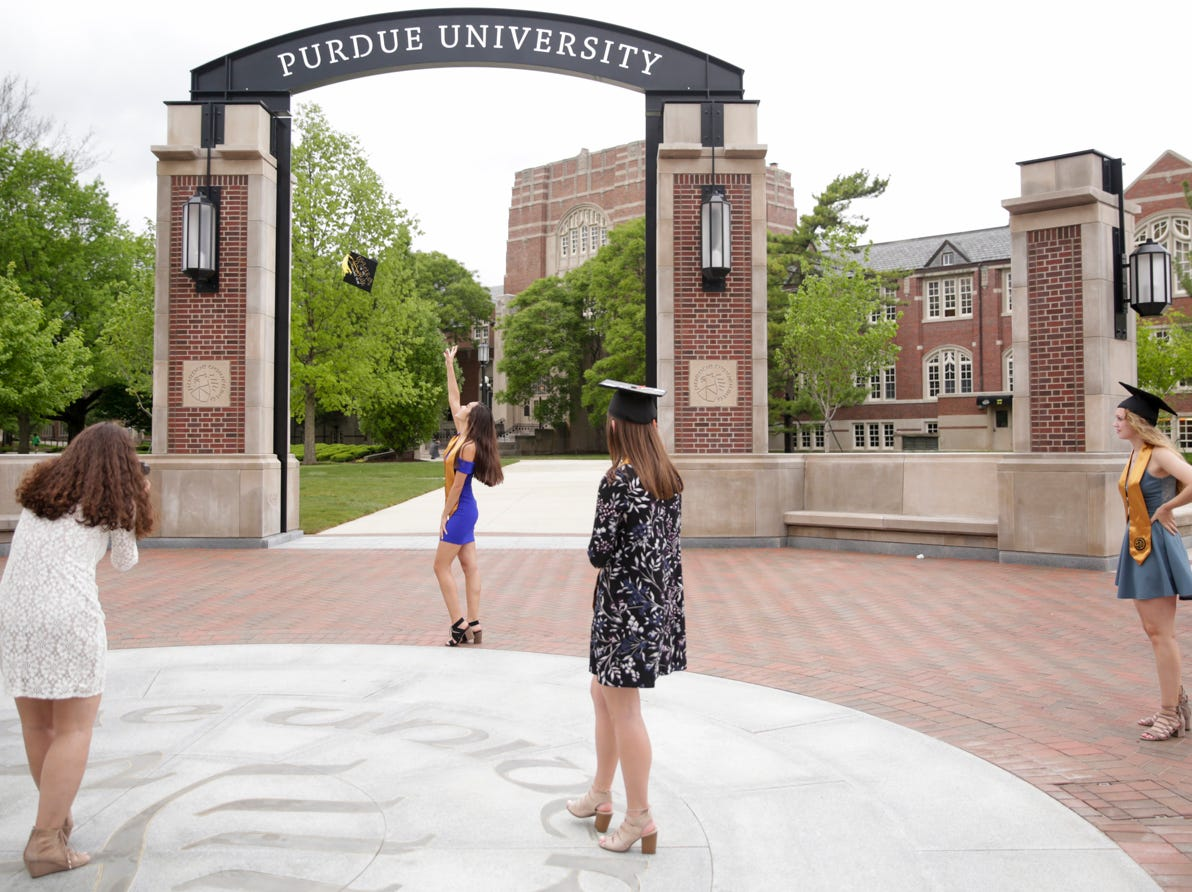 Emily Adanuya, center, throws her cap in the air in front of the new gateway at State and Grant streets, Thursday, May 9, 2019, at Purdue University in West Lafayette. Purdue finished its new $1.9 million gateway in time for this weekend's commencement ceremonies. The gateway was built to mark the university's 150th year.