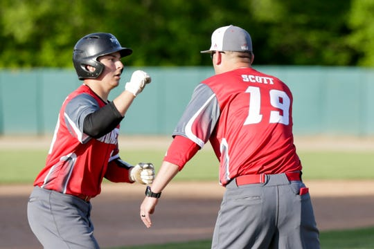 Rossville pitcher Payton Dennison (28) reaches out to fist bump Rossville head coach Brad Scott after hitting a solo homerun during the fifth inning of a high school baseball game, Wednesday, May 8, 2019, at McCutcheon High School in Lafayette. Rossville won, 7-6.
