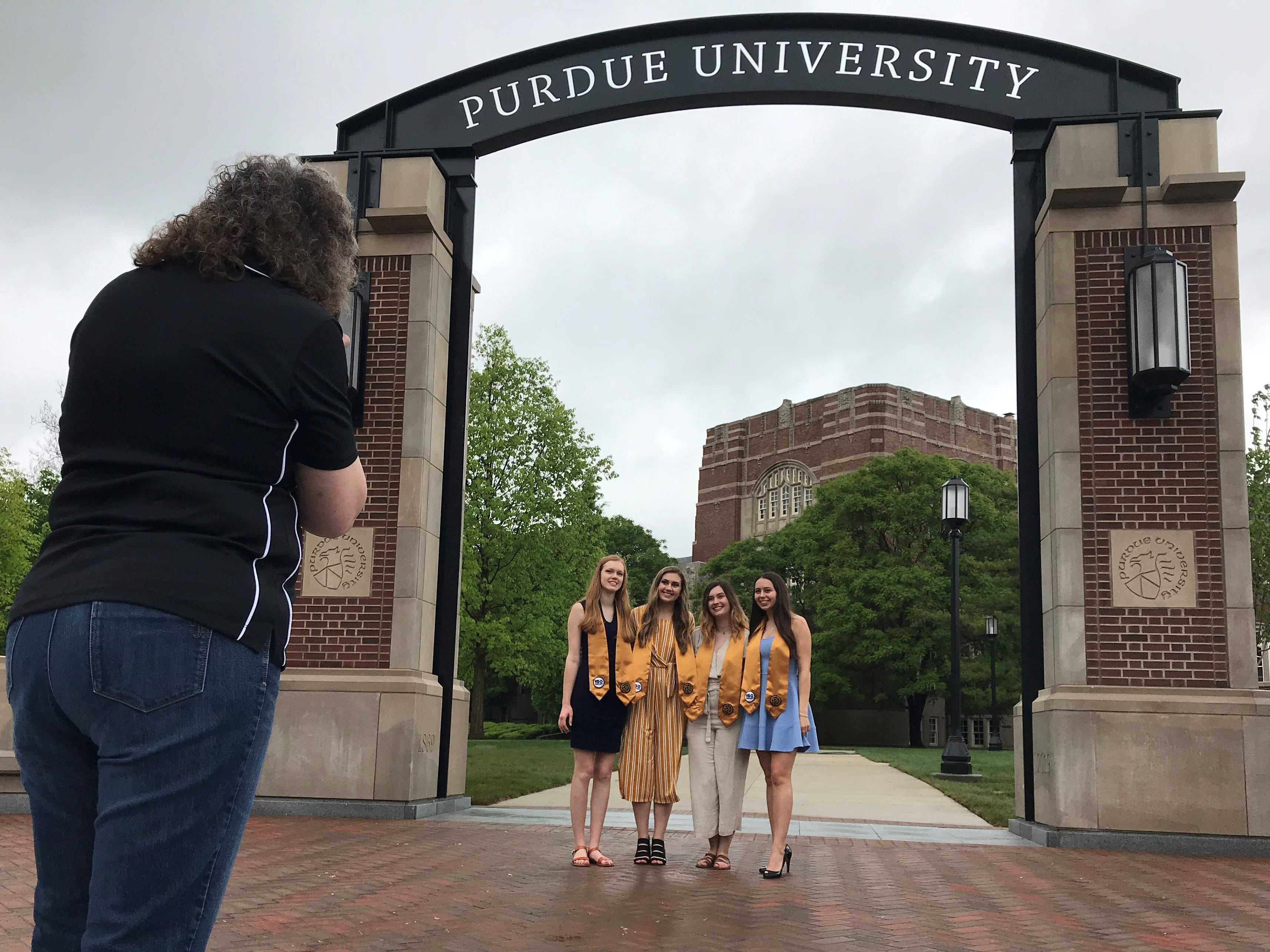 Donna Pitts, a Purdue graduate from Milan, takes a pre-graduation photo of Purdue seniors, from left, Brooke Siefert, Sarah Pitts, Emily Overway and Rachel Sims, as they pose next to Purdue's new gateway at State and Grant streets on Thursday, May 9, 2019. Purdue finished construction of the $1.9 million gateway Wednesday evening in time for this weekend's commencement ceremonies.