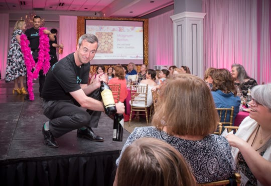 A shoe guy at Wine, Women and Shoes 2018 helps a table of guests.