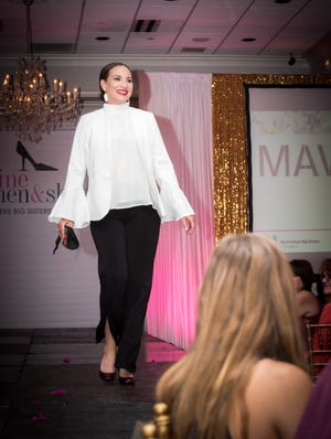 A model at Wine, Women and Shoes 2018 walks the runway.