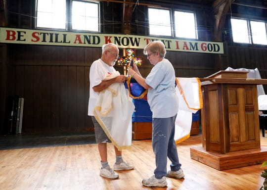 Ray Gerren, left, and Bertie Lacey put a new Christian flag on a pole as they stand on the stage of the renovated Davis Auditorium Thursday, May 9, 2019, at the Lancaster Campground in Lancaster.