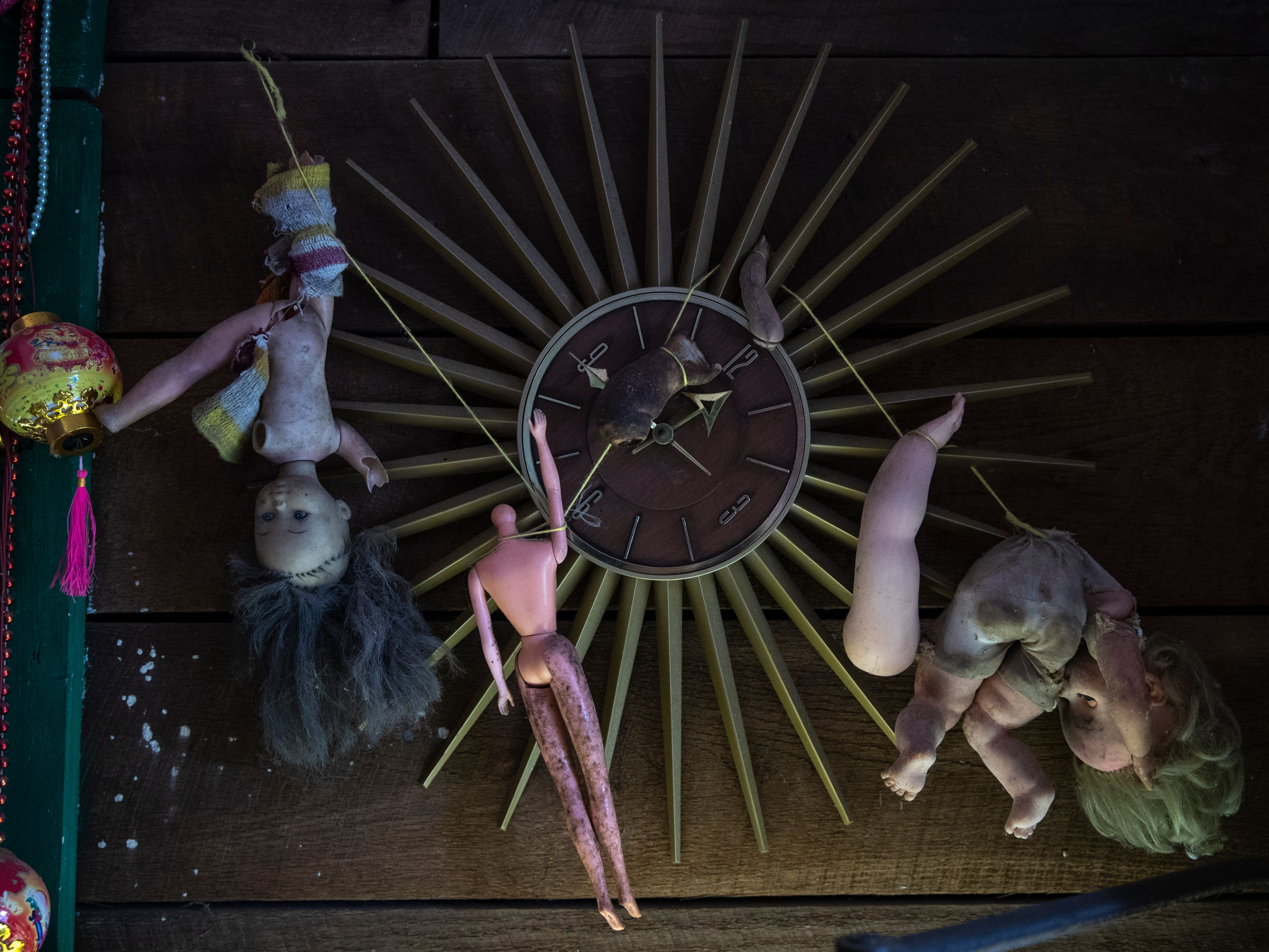Baby dolls, ornaments and beads hang from an antique clock in the Curation Facility #1 at the Home for Wayward Babydolls. April 19, 2019