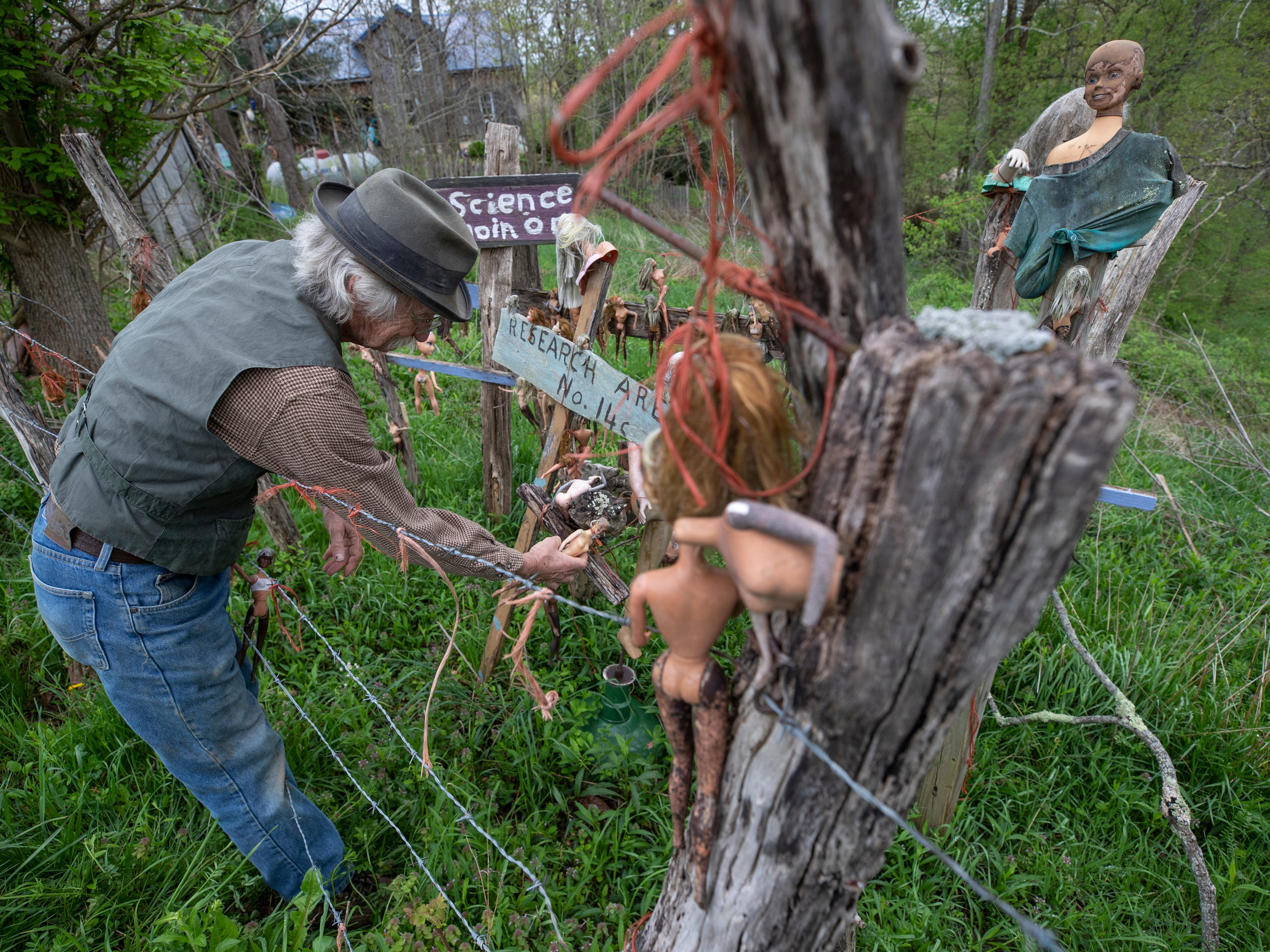 Cecil Ison adjusts some of the dolls in an area devoted to Barbie and Barbie wanna-be dolls at the Home for Wayward Babydolls. April 19, 2019