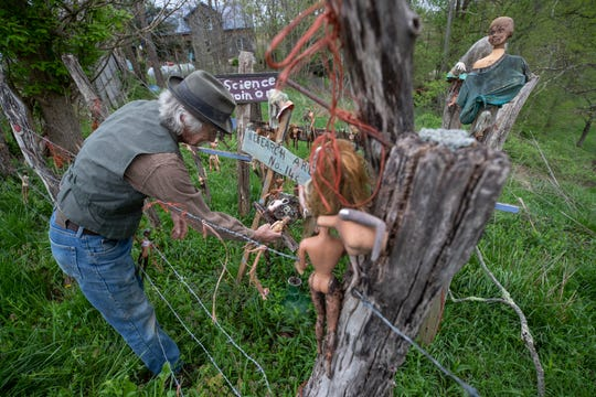Cecil Ison adjusts some of the dolls in an area devoted to Barbie and Barbie wanna-be dolls at the Home for Wayward Babydolls.