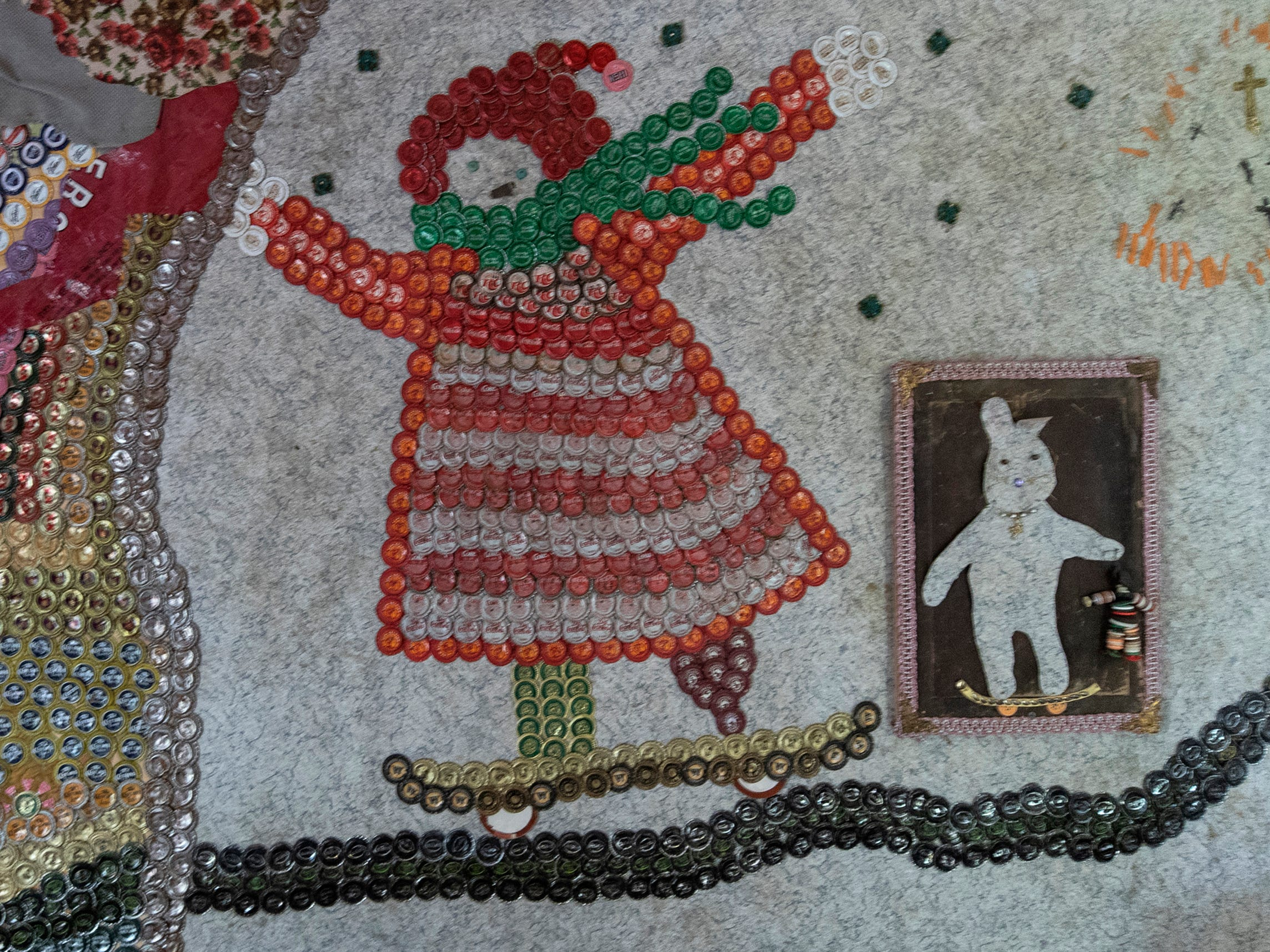 """A mural made of bottle caps by Cecil Ison called, """"Little Red Knit cap girl and her Bunny"""" hangs in the Curation Facility #1, at the Home for Wayward Babydolls. April 19, 2019"""
