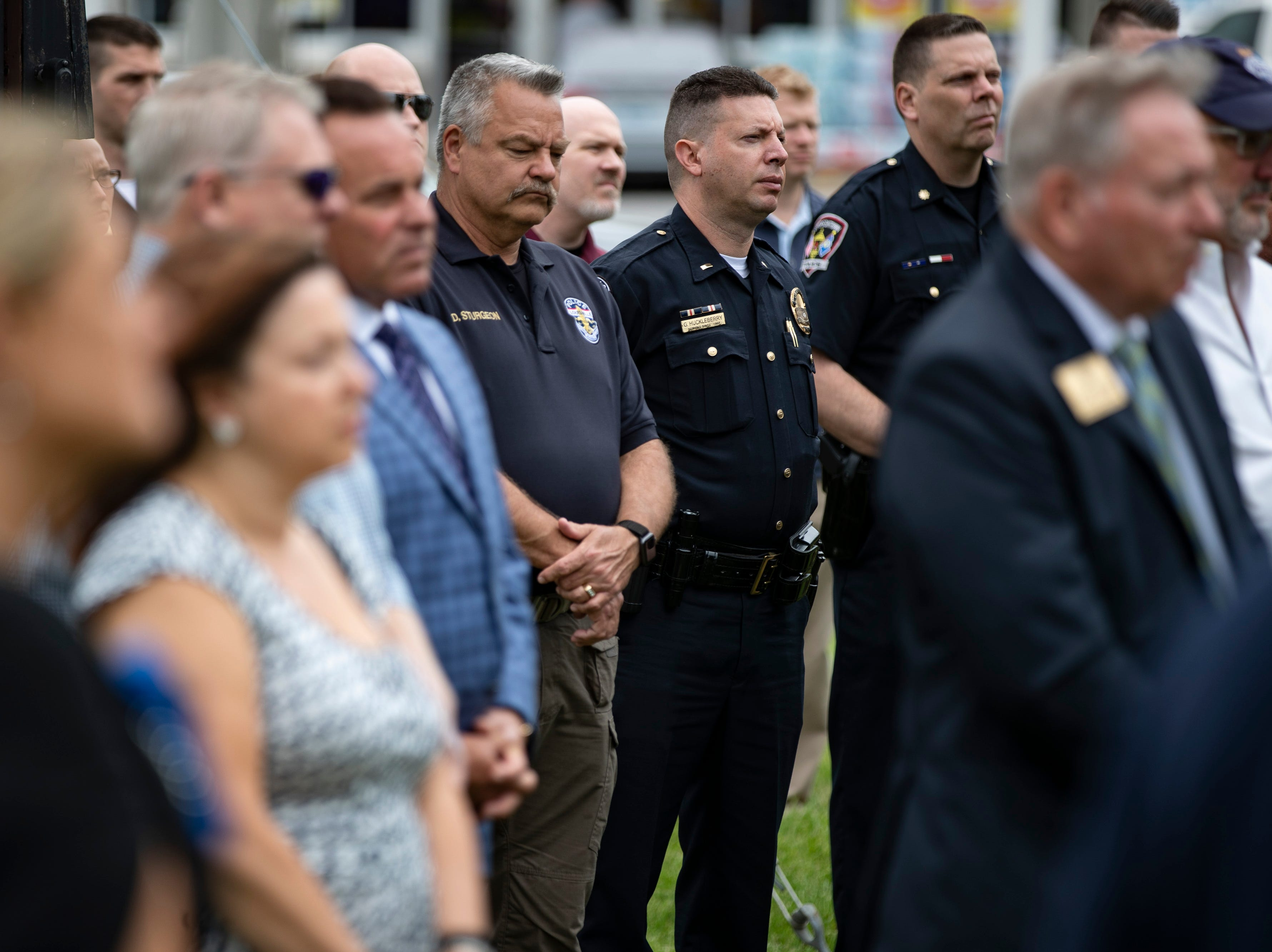 A crowd of police officers and family look on during the renaming of the corner of Stony Brook Drive and Six Mile Lane in Jeffersontown to Peter Grignon Way, in honor of the fallen officer shot during a hit and run stop in 2005. May 9, 2019