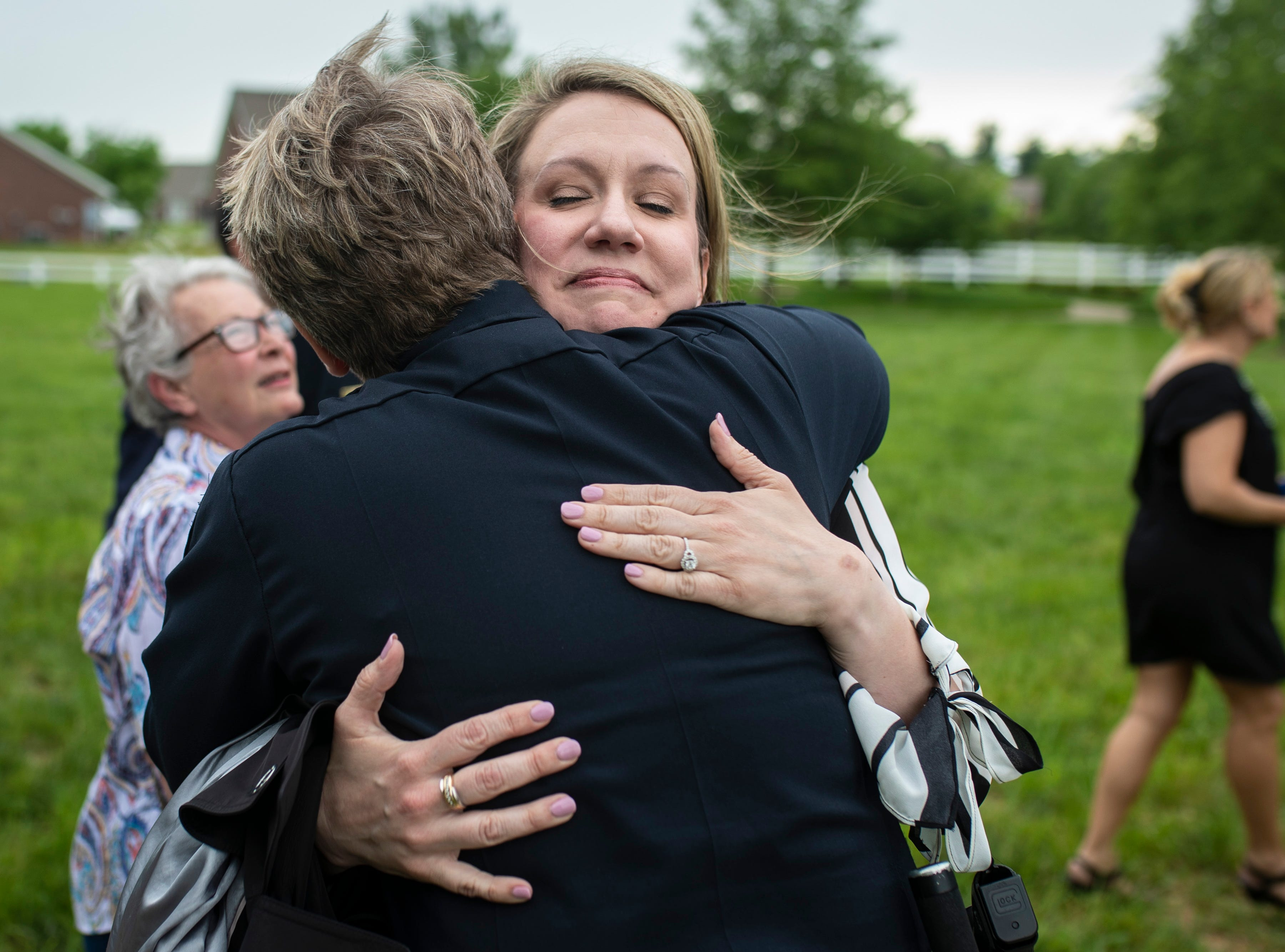 Rebecca Grignon, right, receives a hug from Assistant Chief of Police Shara Parks following the renaming of the corner of Stony Brook Drive and Six Mile Lane in Jeffersontown to Peter Grignon Way, in honor of Rebeccas's late husband and fallen officer shot during a hit and run stop in 2005. May 9, 2019