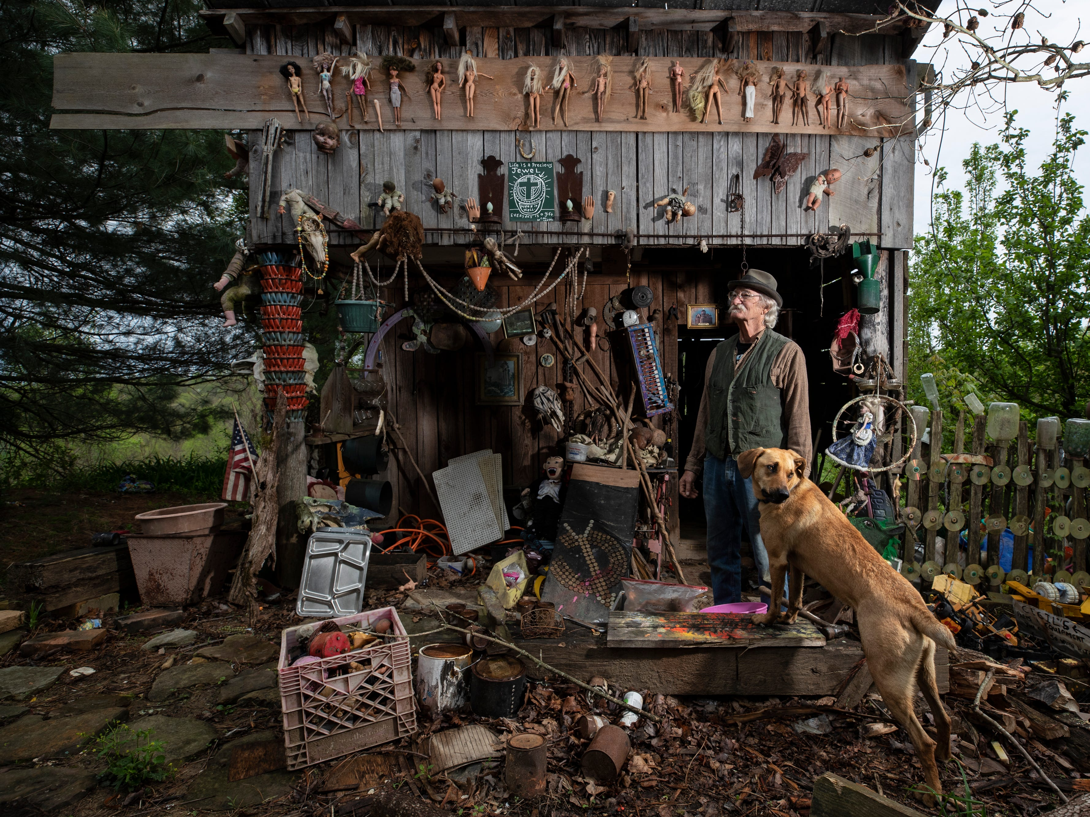 Cecil R. Ison stands with his dog Jabberwocky outside one of the buildings at the Home for Wayward Babydolls. April 19, 2019