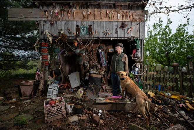 Cecil R. Ison stands with his dog Jabberwocky outside one of the buildings at his Home for Wayward Babydolls in the hills of eastern Kentucky.