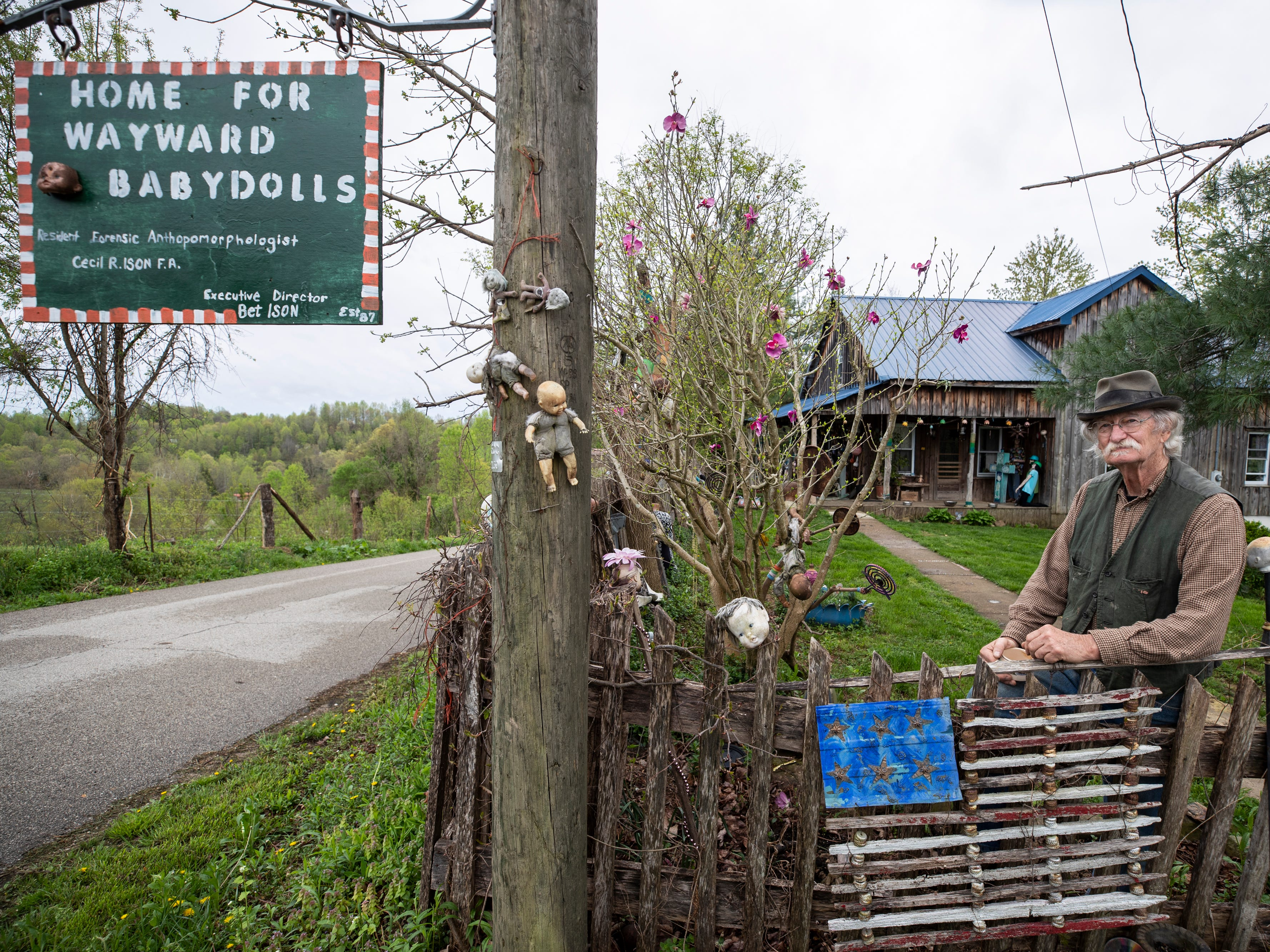 Cecil R. Ison stands a the gate of the Home for Wayward Babydolls. Ison studies abandoned and abused dolls at the home in Elliotville, Ky. April 19, 2019