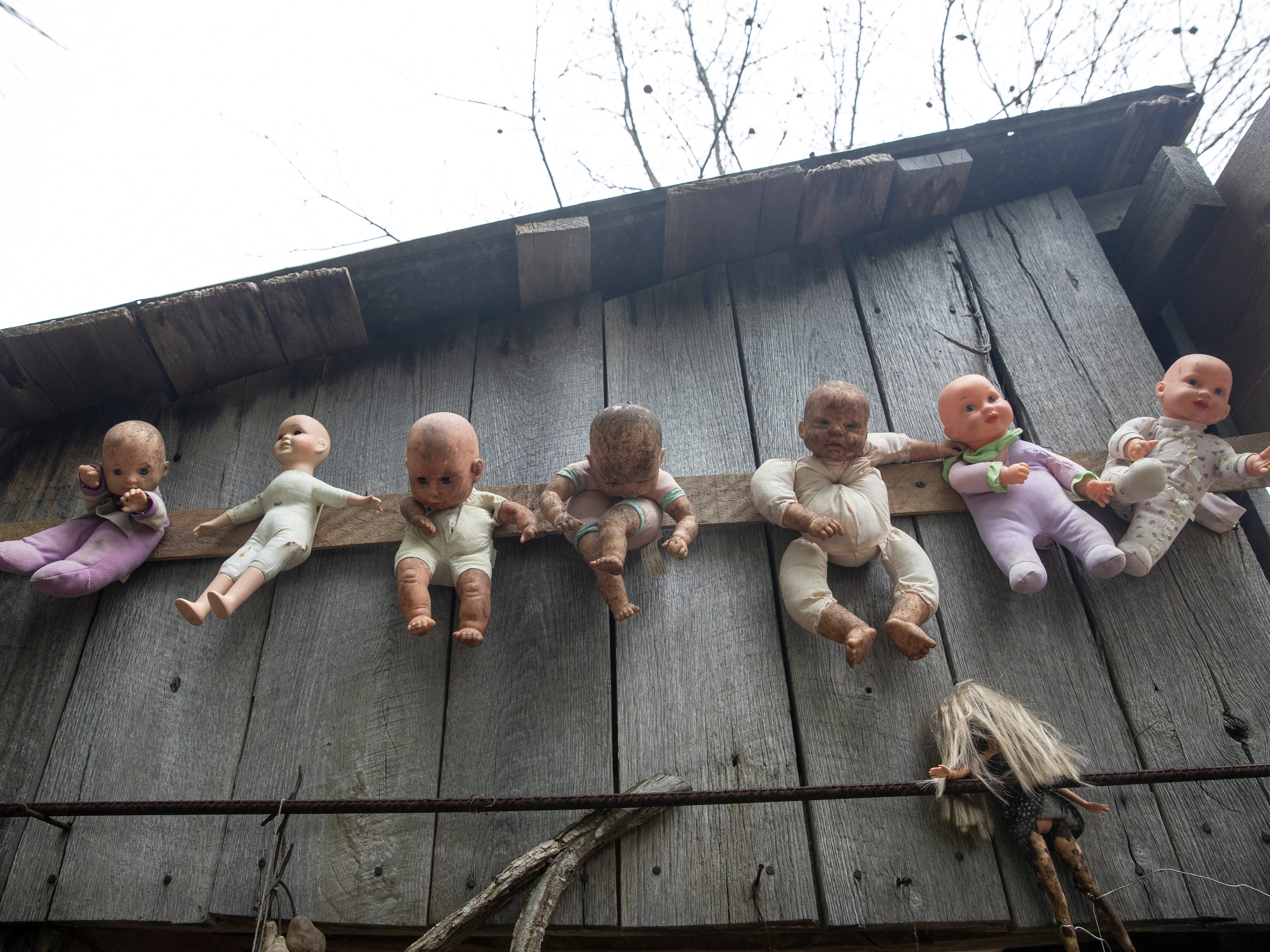 A collection of baby dolls decorate the side of a building at the Home for Wayward Babydolls. April 19, 2019
