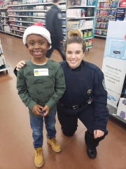"""Lansing Police Explorer's Post Capt. Marymargaret Bradbury poses with a child at the department's annual """"Shop with a Cop"""" event in late 2018."""