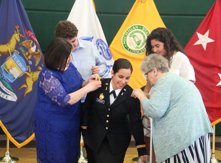 2nd Lt. Dawood's family affixing her rank insignia (shoulder boards) to her uniform during the commissioning ceremony.  From left to right, Ms. Karryn Dawood, Sam Dawood, 2nd Lt. Naomi Dawood, Ms. Sue Gering, and Suzy Dawood (2nd. Lt Dawood's mother, brother, herself, grandmother and sister, respectively).