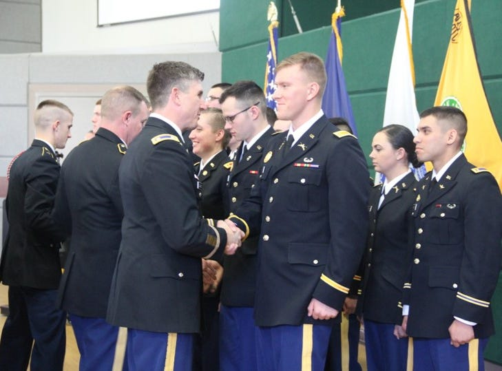 Lt. Col. Jason DeGeorge presents the Department Challenge Coin to 2nd Lt. Justin Roney.  During the ceremony Lt. Col. DeGeorge and Master Sgt. Keith Barber presented the department challenge coin to all graduates of the program for their exceptional achievement or service.