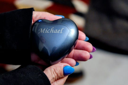 Joanna Wohlfert holds a heart-shaped container that holds a portion of her son's ashes at her home on Monday, April 29, 2019, in Lansing. Wohlfert's 13-year-old son Michael Martin died on Jan. 25, 2019, at Sparrow Hospital, two days after attempting suicide in his home. Wohlfert says her son was bullied in the months leading up to his death.