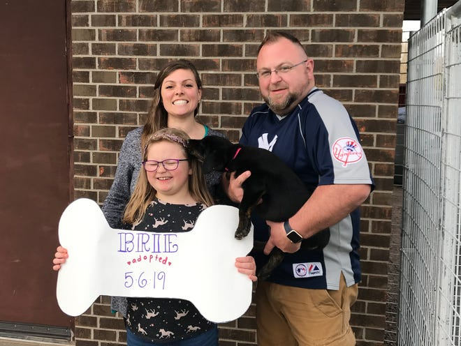 Mark Theobald and his family pose with their new puppy Brie.