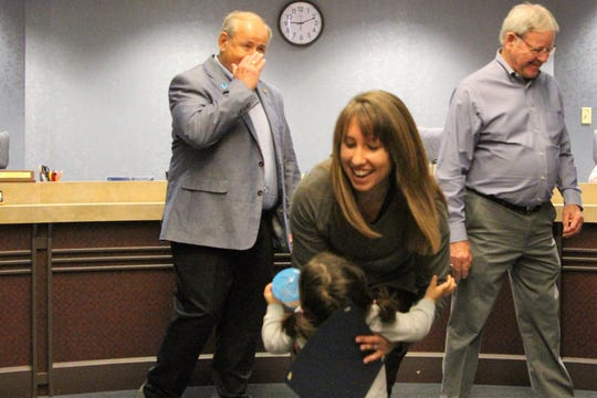 Jennifer McMurray picks up her 18-month-old foster daughter, who entered her home in March, during the signing of a proclamation by Marion County Commissioners honoring National Foster Care Month.