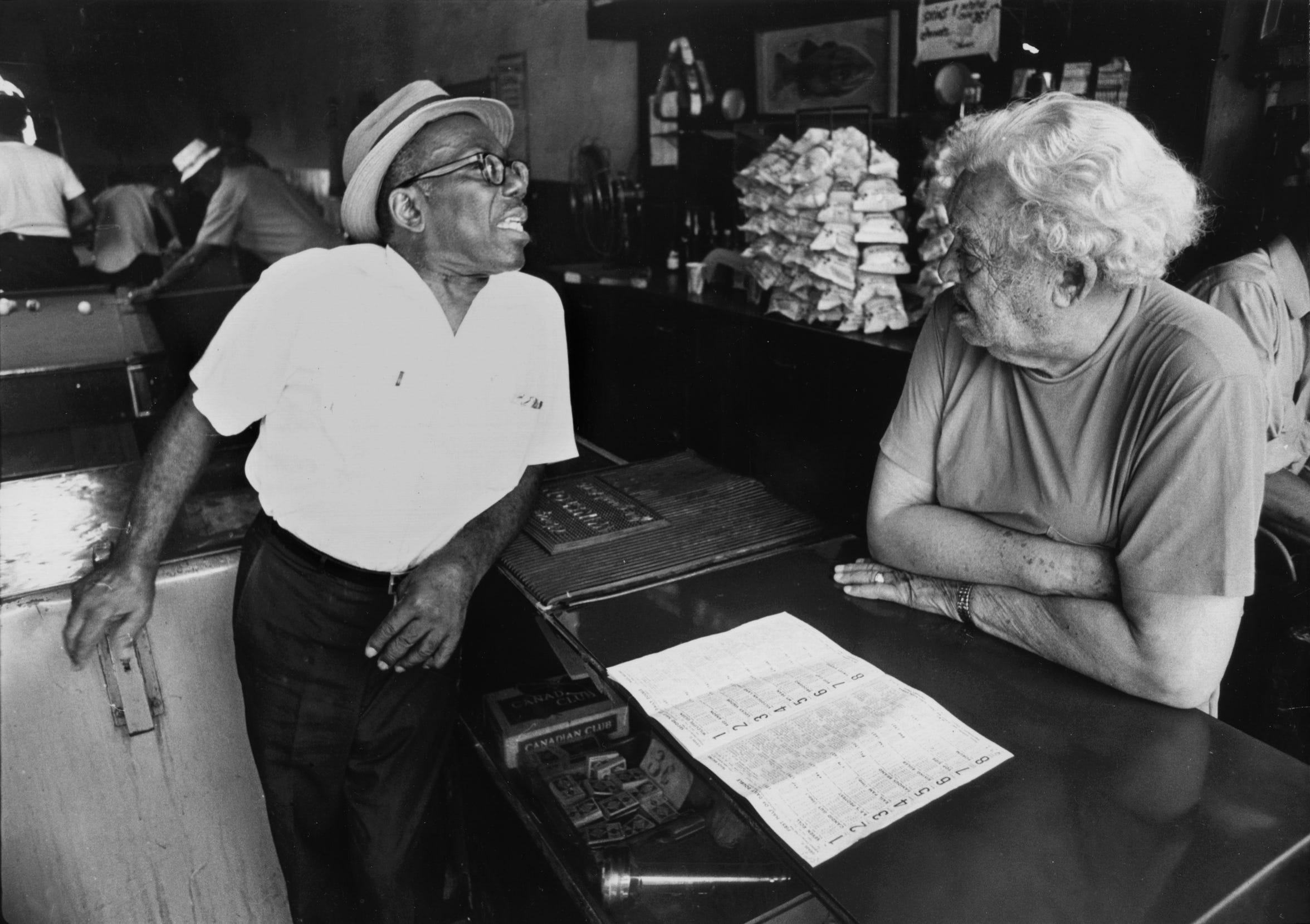 "Nat D. Williams talks to Robert Henry in Henry's pool room on Beale Street in July 1974. The segregated South became colorblind on the airwaves of WDIA, beginning with deejay Nat D. Williams and the 1948 debut of his ""Tan Town Jamboree"" program. Born on Beale Street in 1907, Williams passed away in 1983."