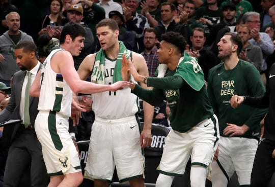 Bucks forward Giannis Antetokounmpo (right) greets teammate Ersan Ilyasova as Brook Lopez (center) looks on during Milwaukee's 116-91 win over the Celtics on Wednesday night.