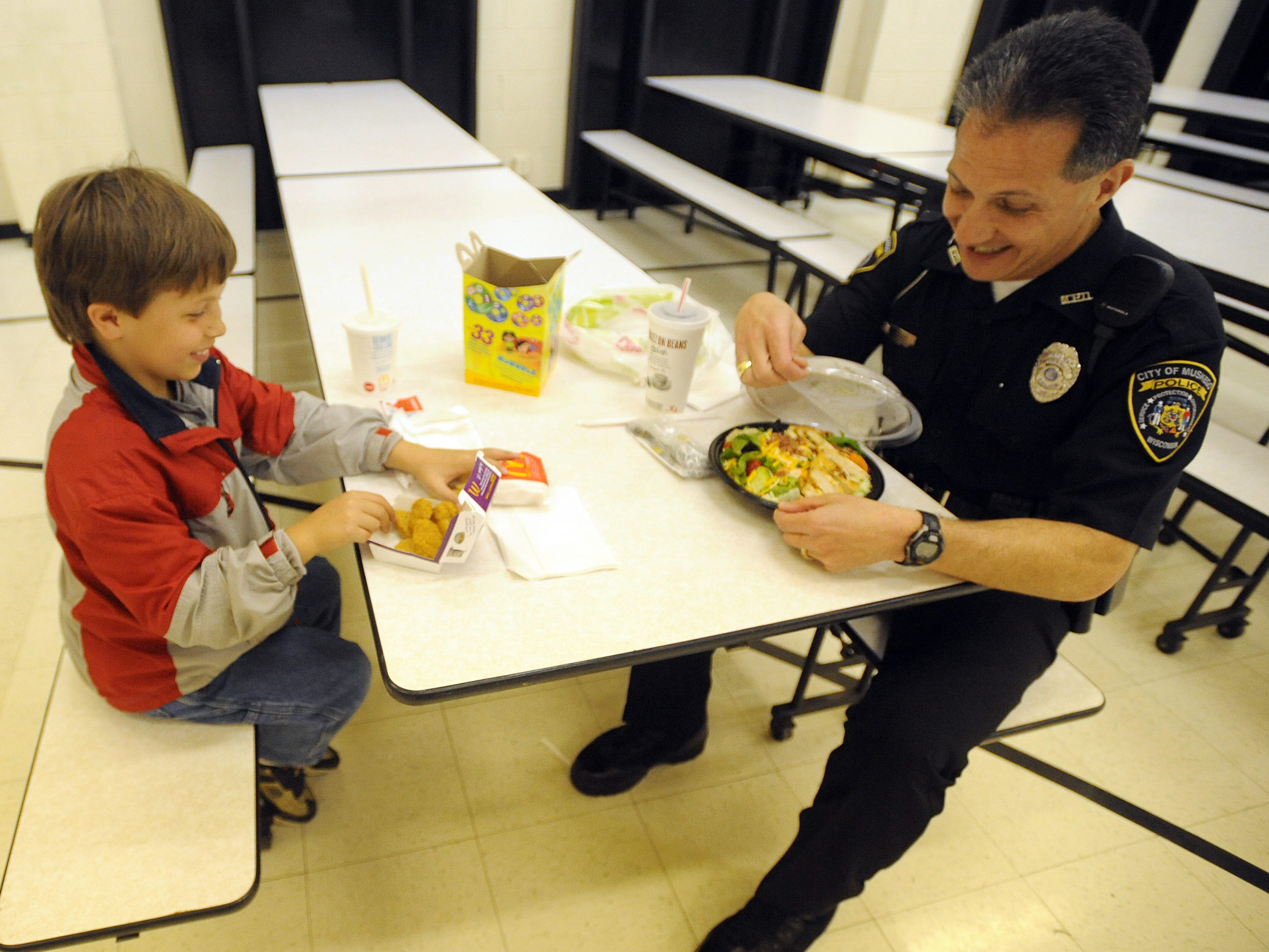 """Police officers eat lunch too,"" said Muskego Police Officer Gary Leon as he sits down for lunch Wednesday, May 6, 2009, with Colten Kersky, a second-grader at Muskego Elementary School. Colten won the lunch, along with a ride to school in Leon's police car, through a raffle at the school's spring carnival."