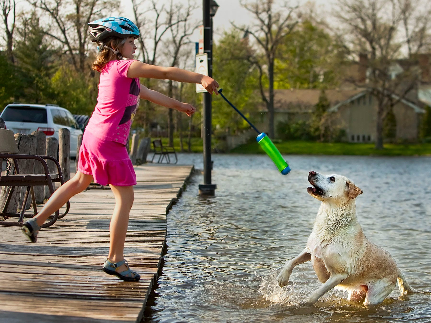 "Emma Audley, 6, of Oconomowoc plays fetch with ""Maddie"" her 9-year-old yellow lab May 12, 2009, in the cool waters of Fowler Lake."