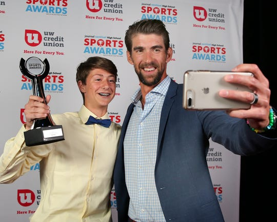 Mukwonago's Cody Peters, the 2019 I AM SPORT winner, gets a selfie with Michael Phelps.