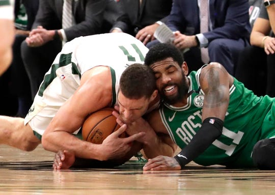 Bucks center Brook Lopez and Celtics guard Kyrie Irving fight for a loose ball Wednesday night.