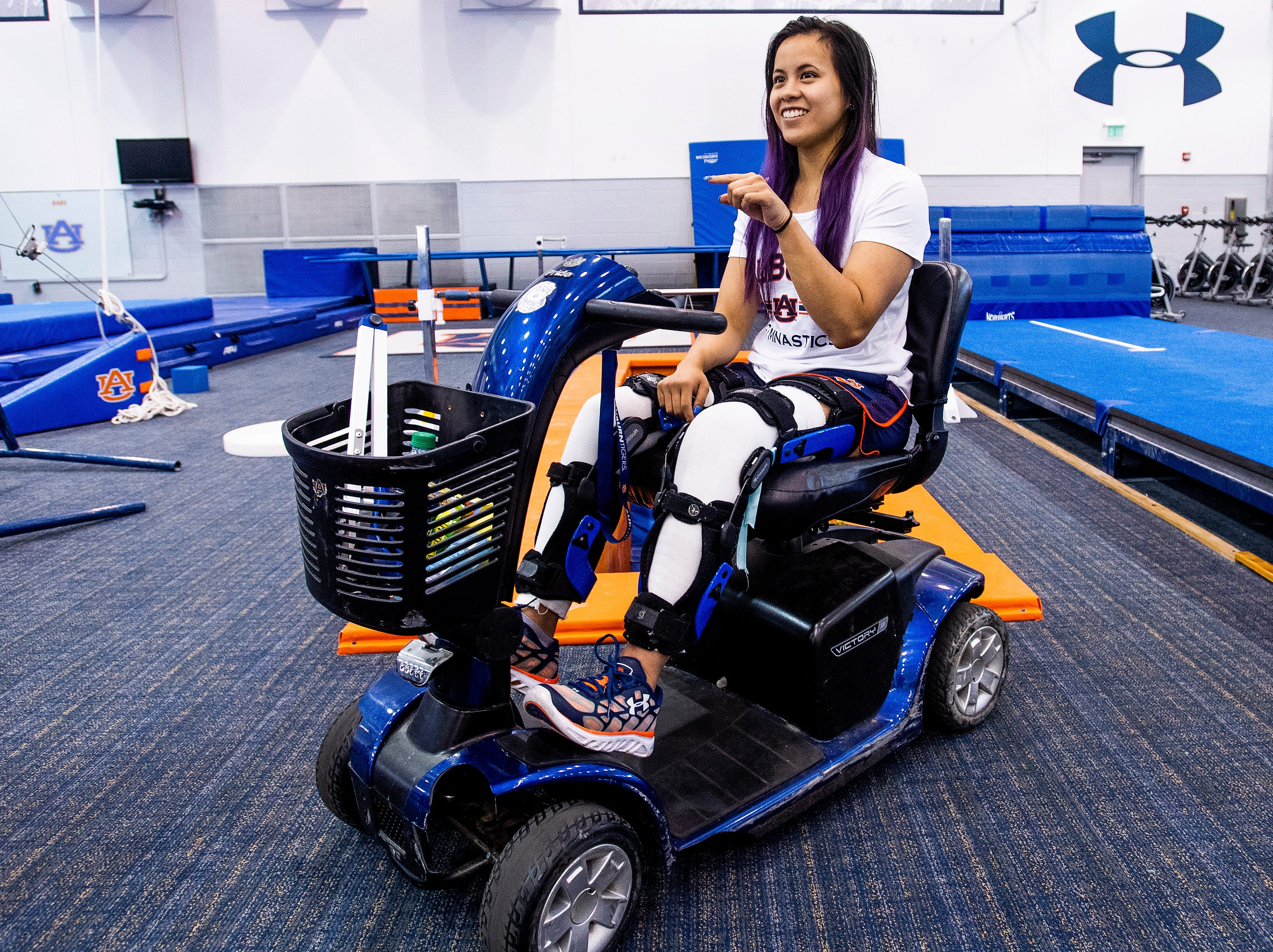 Auburn university gymnast Sam Cerio gets around on a scooter in the women's gymnastics practice facility on the AU campus in Auburn, Ala., on Thursday May 9, 2019. Cerio, who recently graduated with a degree in aerospace engineering, dislocated both of her knees and ruptured multiple ligaments in her legs during an NCAA regional semifinal meet.