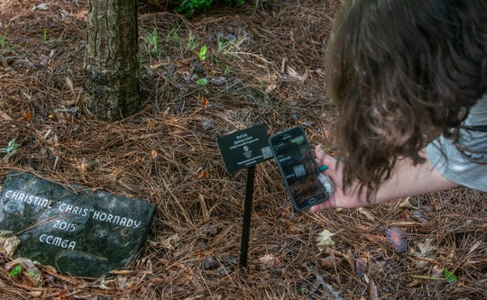 Jacque Foshee, executive director of Montgomery Botanical Gardens, demonstrates how a code on the sign for this red oak allows visitors to get information about the plant. The public is invited to activities at Montgomery Botanical Gardens in Oak Park during National Public Gardens Week on May 13-19, 2019.