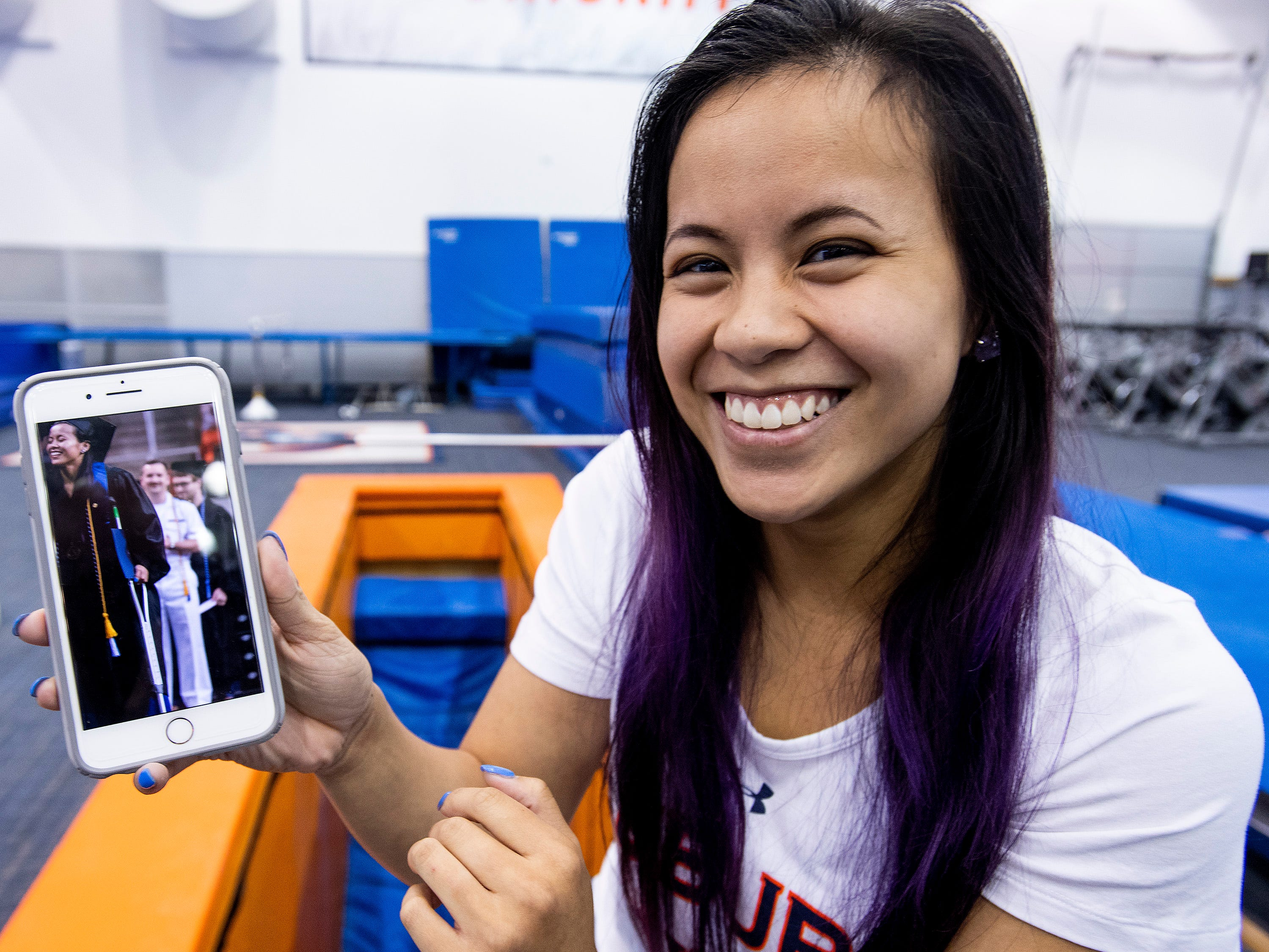 Auburn university gymnast Sam Cerio shows photos of herself walking at her graduation, a week earlier, on the AU campus in Auburn, Ala., on Thursday May 9, 2019. Cerio, who recently graduated with a degree in aerospace engineering, dislocated both of her knees and ruptured multiple ligaments in her legs during an NCAA regional semifinal meet.