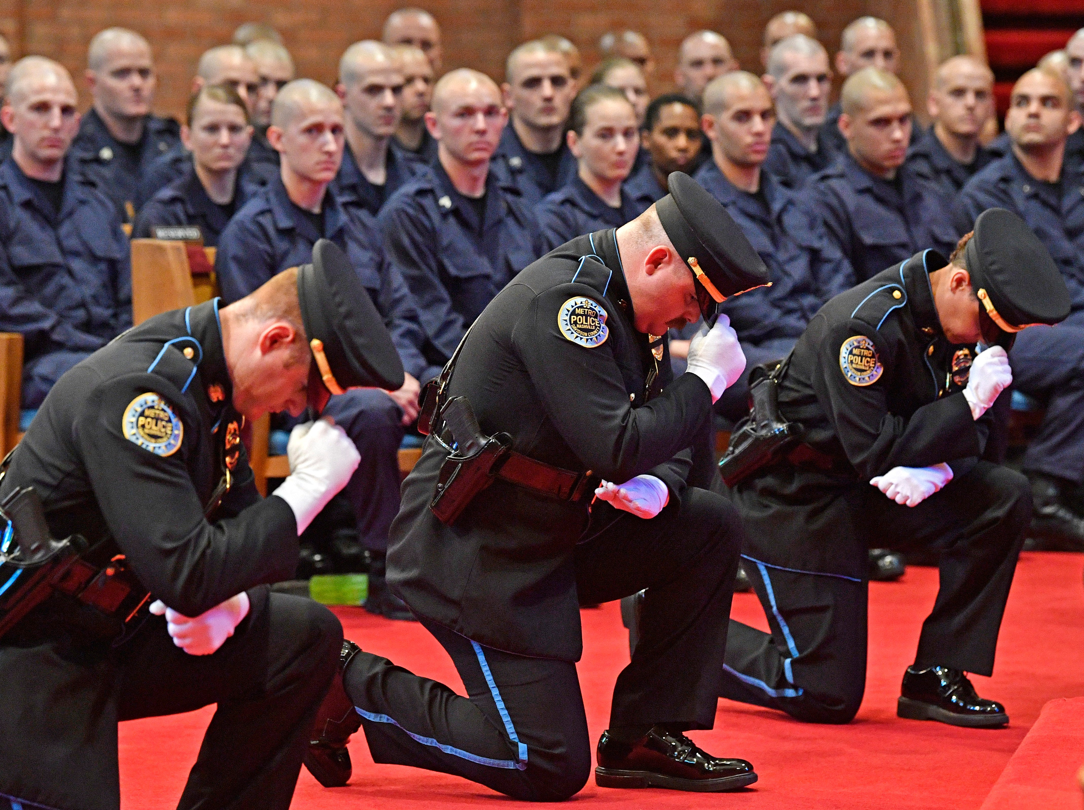 The Police Drill and Ceremony Team kneel in honor of officers that have fallen at the annual memorial service honoring Nashville's police officers who have died in service to the city Thursday, May 9, 2019, in Nashville, Tenn.