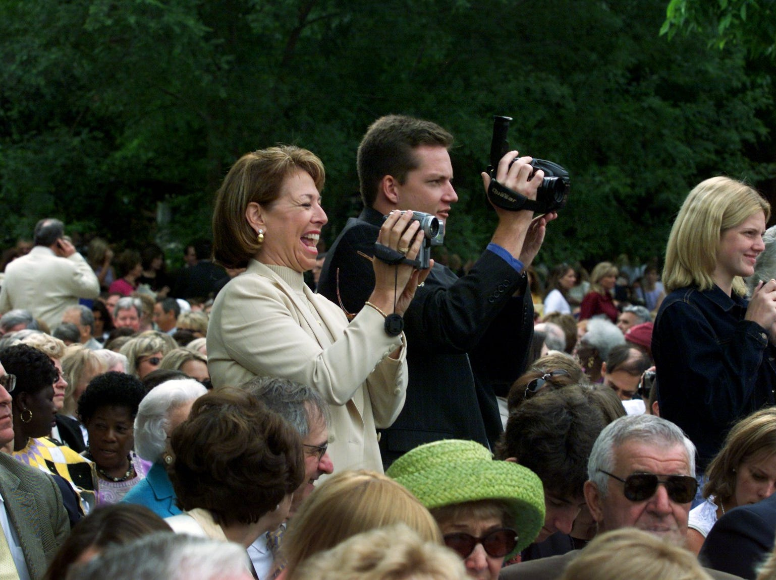 Nancy Walkenhorst, of Joplin, Missouri, videotapes her daughter's boyfriend while Matt Tippy, of Florida, shoots his brother during the 2002 commencement ceremony at Vanderbilt University.