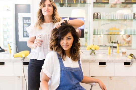 Drybar founder Alli Webb styles a client's hair.