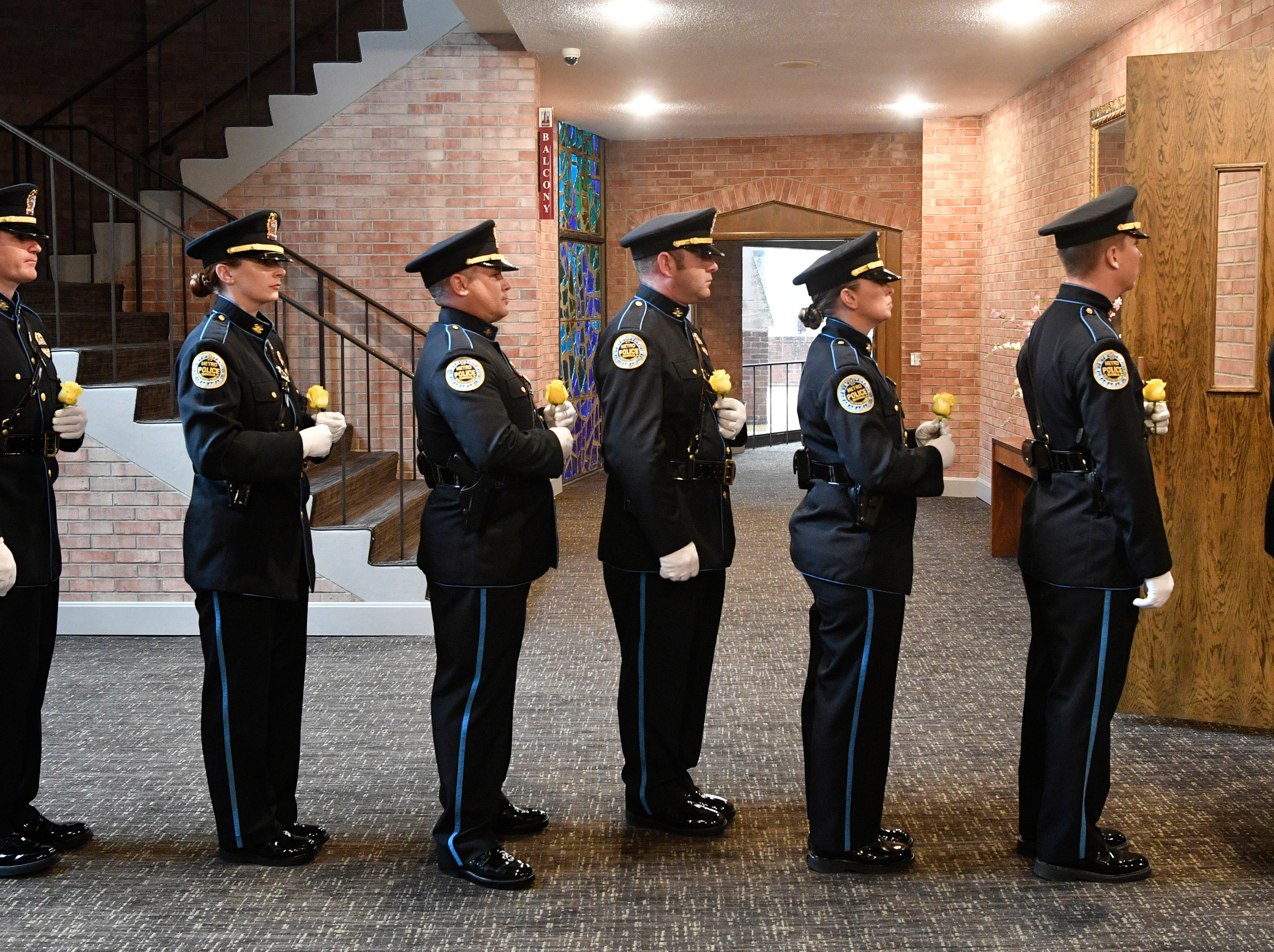 Members of police Drill and Ceremony Team carry a yellow rose each in honor of a fallen officer at the annual memorial service honoring Nashville's police officers who have died in service to the city Thursday, May 9, 2019, in Nashville, Tenn.