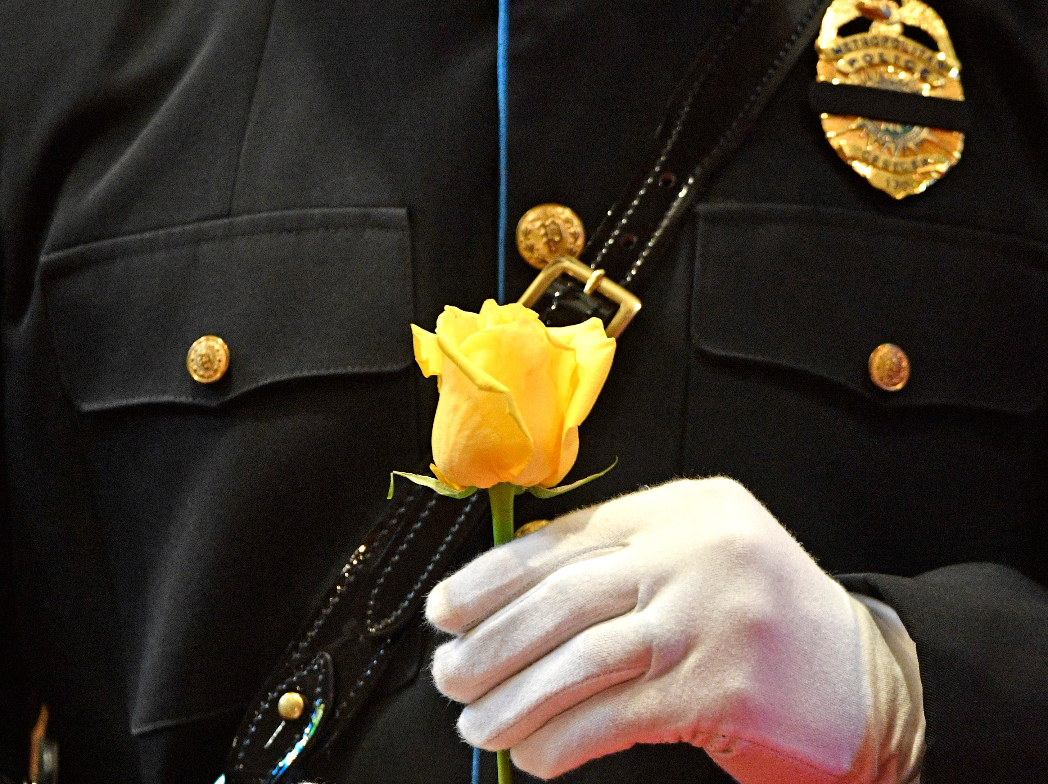 A member of the honor guard carries a yellow rose in honor of a fallen officer at the annual memorial service honoring Nashville's police officers who have died in service to the city Thursday, May 9, 2019, in Nashville, Tenn.