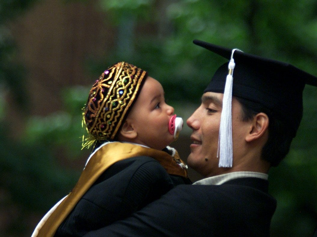 Hassanboi Mirzaev takes a break during 2002 Vanderbilt commencement activities to watch his daughter Kamila, 9 months. Both Mirzaev and his wife graduated with master's degrees, his in economics and hers in engineering. Kamila wears a hat from their native Uzbekistan.