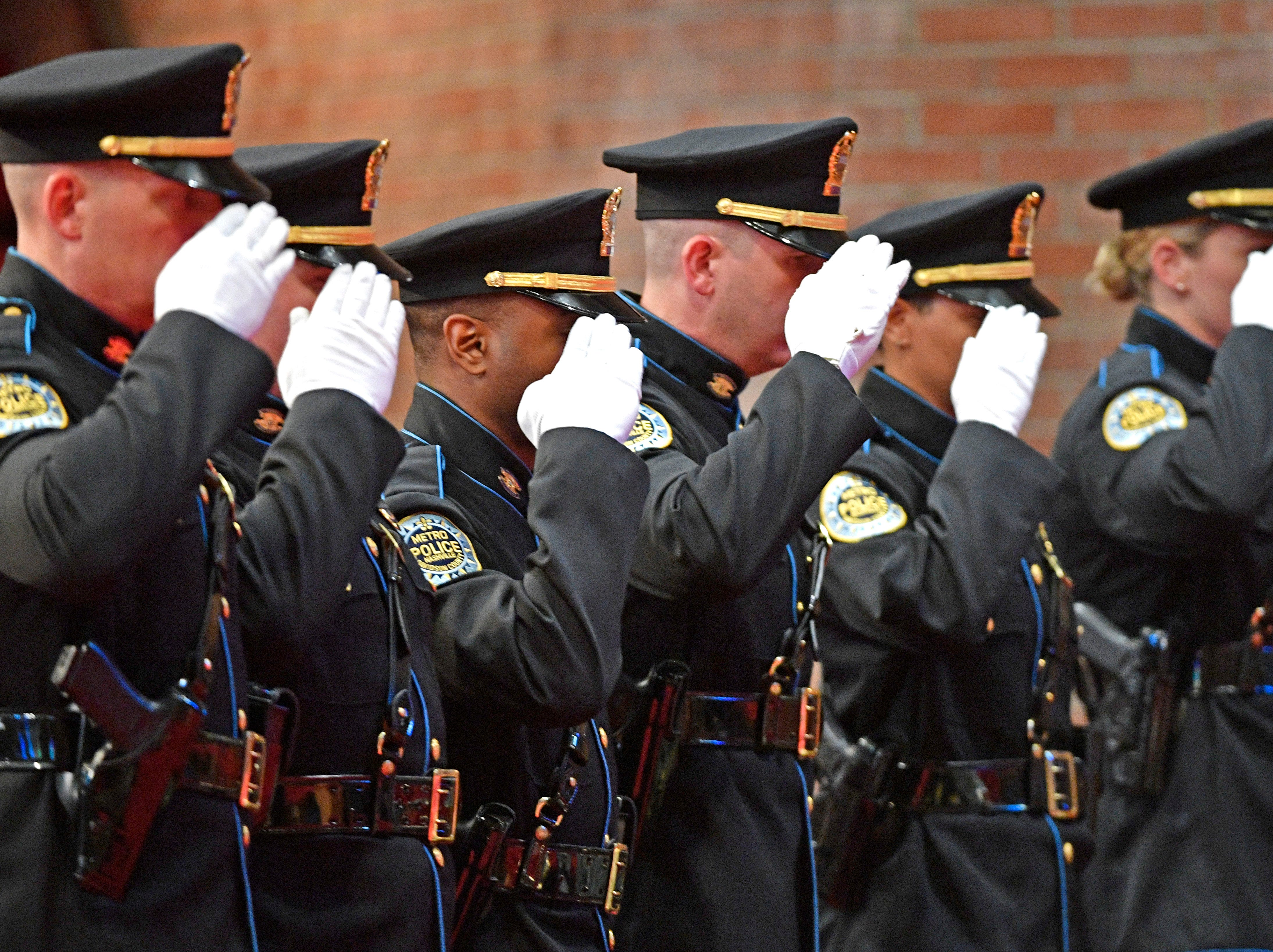Members of the Police Drill and Ceremony Team salute the photos of fallen officers at the annual memorial service honoring Nashville's police officers who have died in service to the city Thursday, May 9, 2019, in Nashville, Tenn.