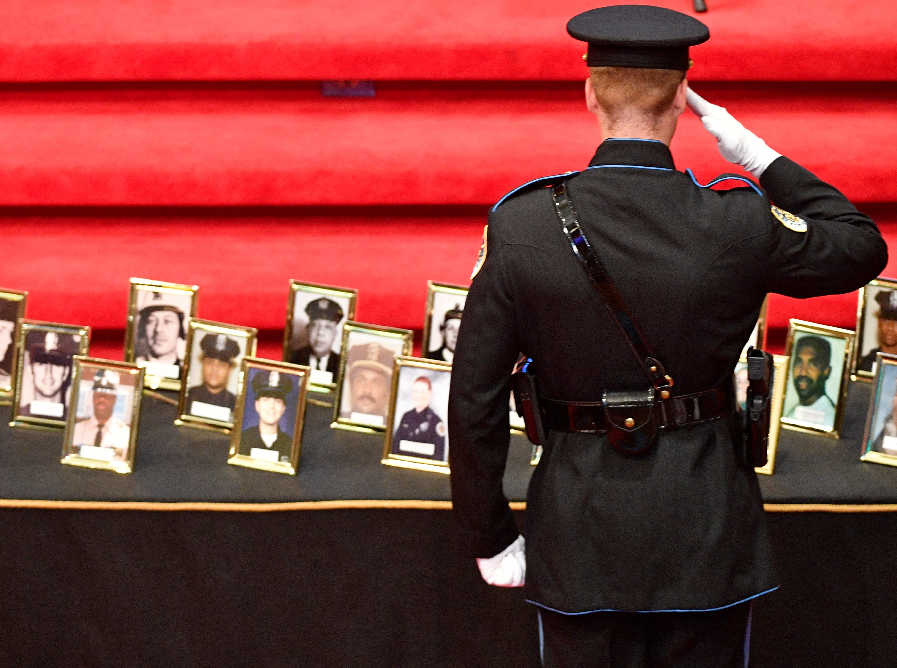A member of the Police Drill and Ceremony Team salutes the photos of fallen officers at the annual memorial service honoring Nashville's police officers who have died in service to the city Thursday, May 9, 2019, in Nashville, Tenn.
