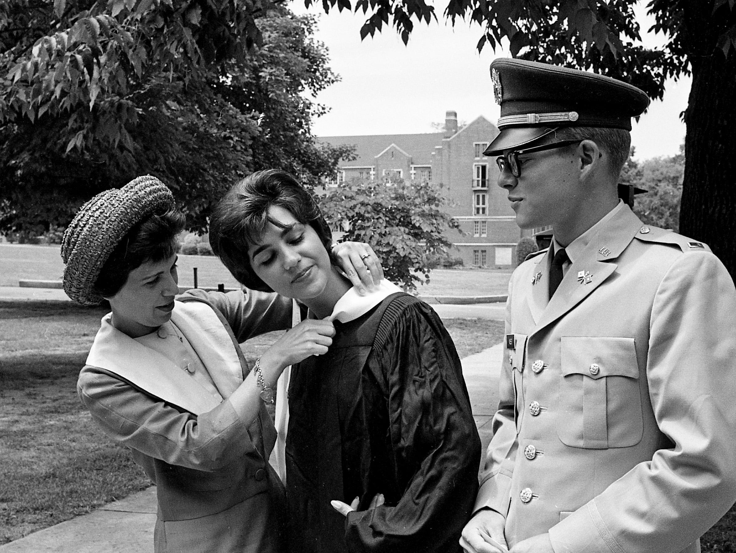Tom West, right, of Louisville, Kentucky, one of the students who graduated from Vanderbilt University on June 3, 1962, watches Mrs. Camille Thomas, left, of Florence, South Carolina, adjust the graduation gown of her sister, Peggy Oms of New Orleans.