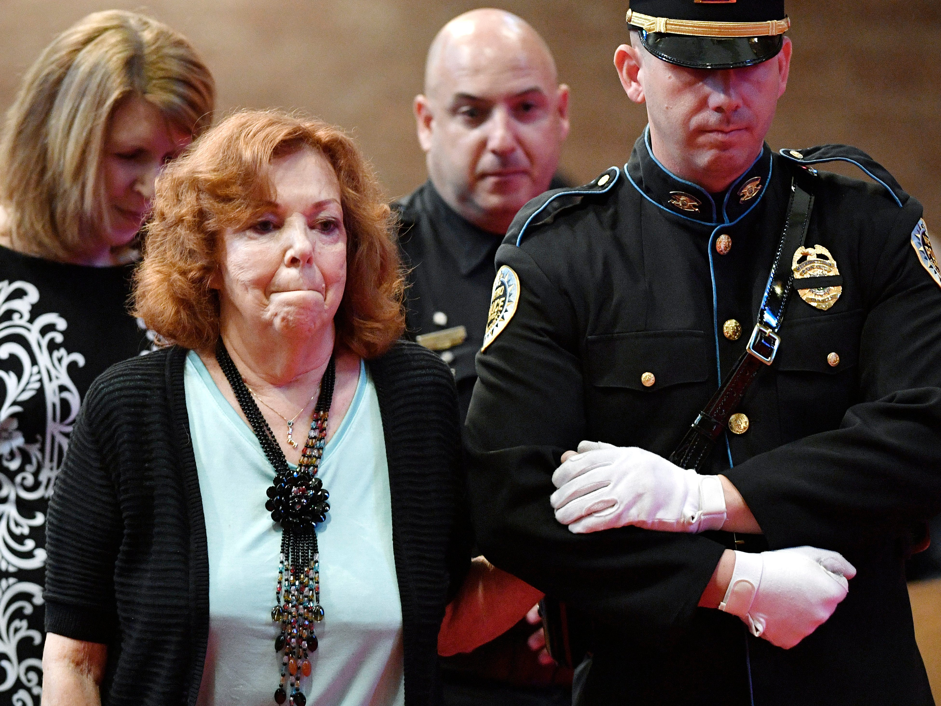 Esther Connell, mother of Eric Mumaw who died in 2017, is escorted to the front to lay a yellow rose beside the photo of her son at the annual memorial service honoring Nashville's police officers who have died in service to the city Thursday, May 9, 2019, in Nashville, Tenn.