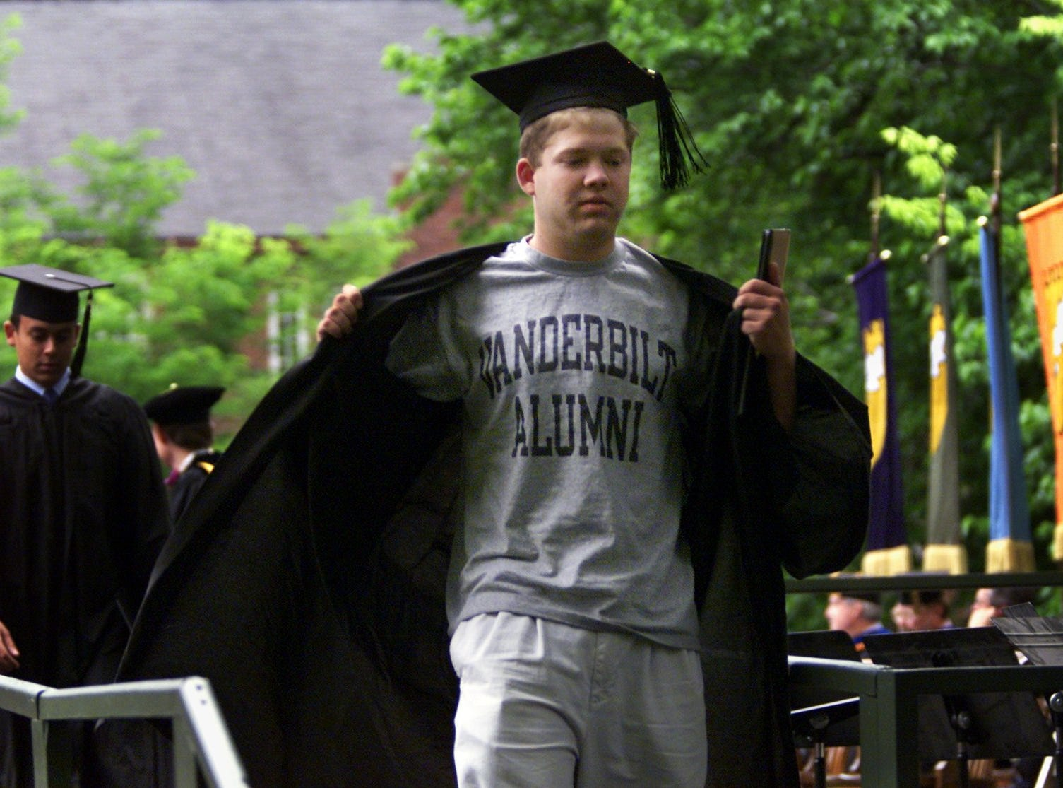 David Carlson opens his graduation robe to flash a Vanderbilt Alumni T-shirt as he crosses the stage with his diploma at Vanderbilt's 2002 commencement. Carlson, from Houston, Texas, received a Bachelor of Arts in interdisciplinary studies: communications.