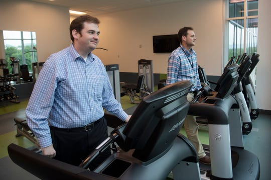 John Ledgewood and Jackson Redditt walk on the treadmills inside the fitness room at One Franklin Park due to the rain weather outside.